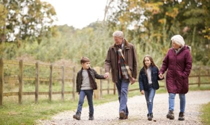 Grandparents With Grandchildren On Autumn Walk In Countryside Together